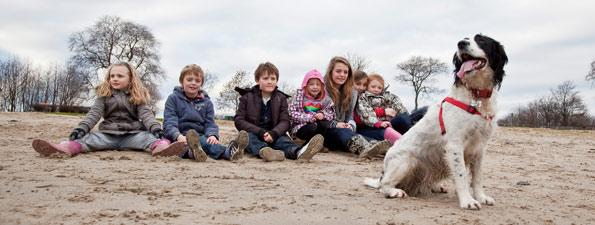 children sitting on beach with black and white dog