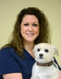 female veterinary technician holding white dog
