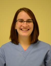 female veterinary technician wearing blue scrub top