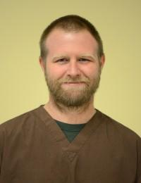 male veterinary technician wearing brown scrub top